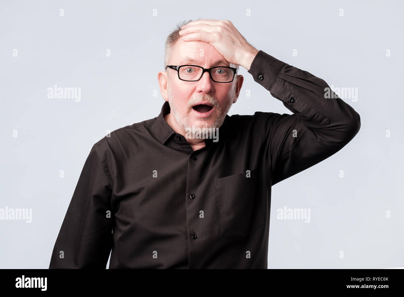 Senior man in black shirt putting his hand on the forehead remembering something - Stock Image