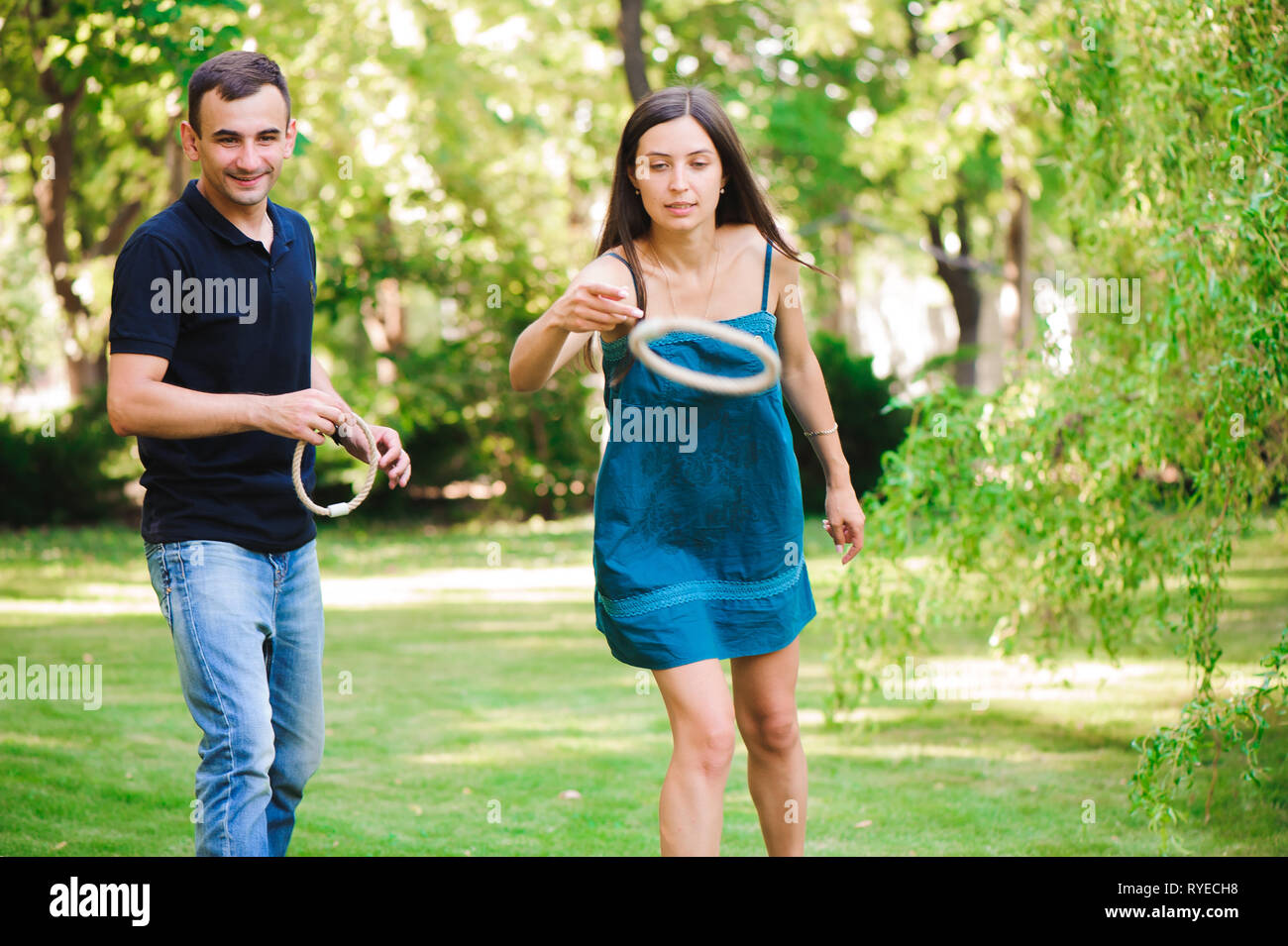 Guy and girl compete in the ring toss - Stock Image