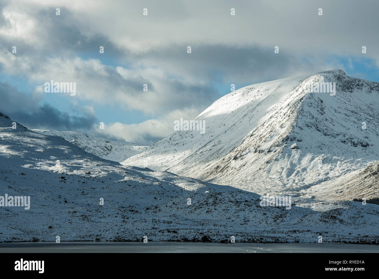 Rannoch Moor in the Scottish Highlands under snow in February. The photo shows snow covered mountains with cloud shadows on them. - Stock Image