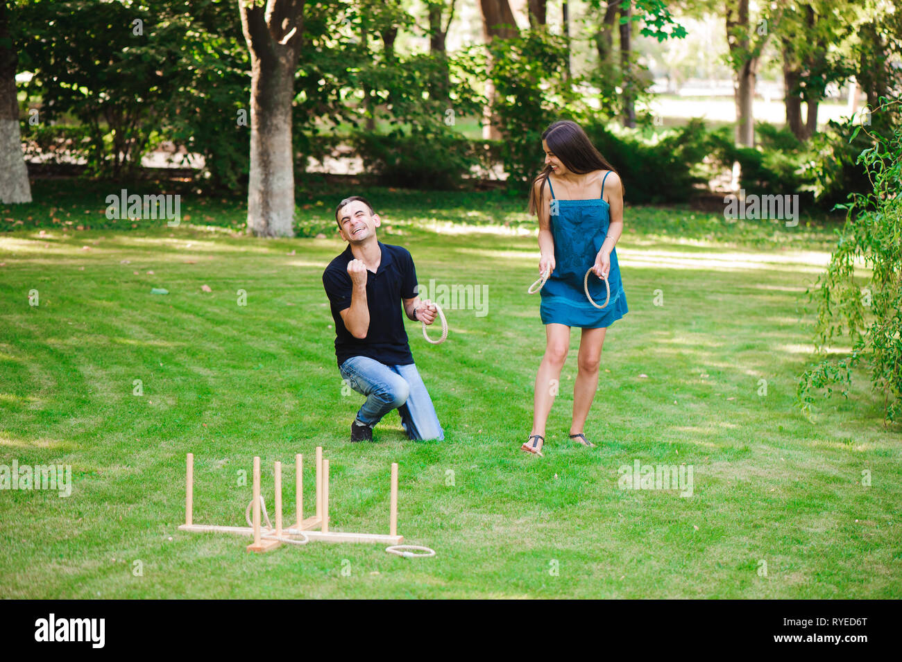 Guy and girl compete in the ring toss. - Stock Image