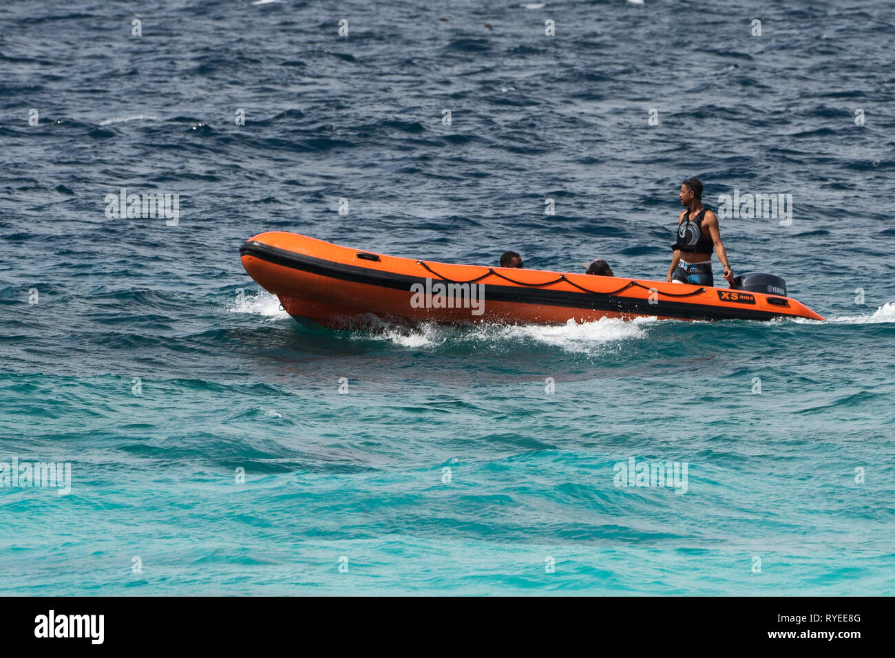 A rubber dinghy boat lands on a beach of Aride Island, Seychelles. Aride Island is the northernmost granitic island in the Seychelles (Bird Island is  - Stock Image