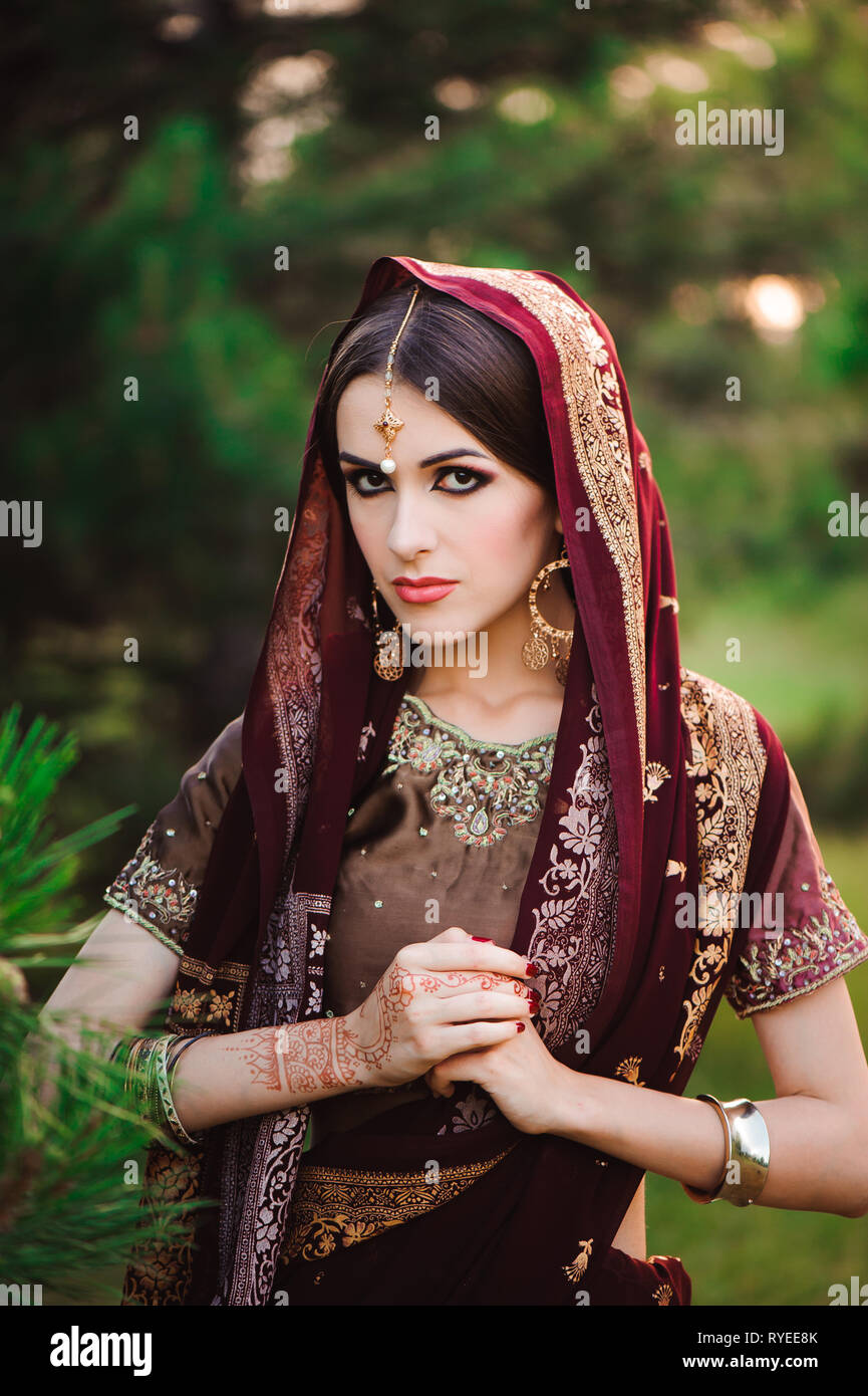 14be066463 Beautiful young caucasian woman in traditional indian clothing sari with  bridal makeup and jewelry and henna
