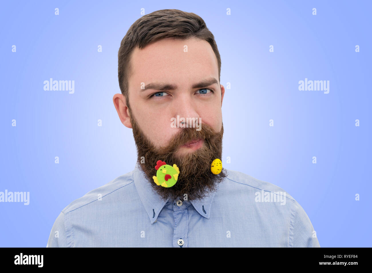 a3140fca5 Portrait of handsome bearded man with decorated beard for Easter on blue  background. Happy Easter