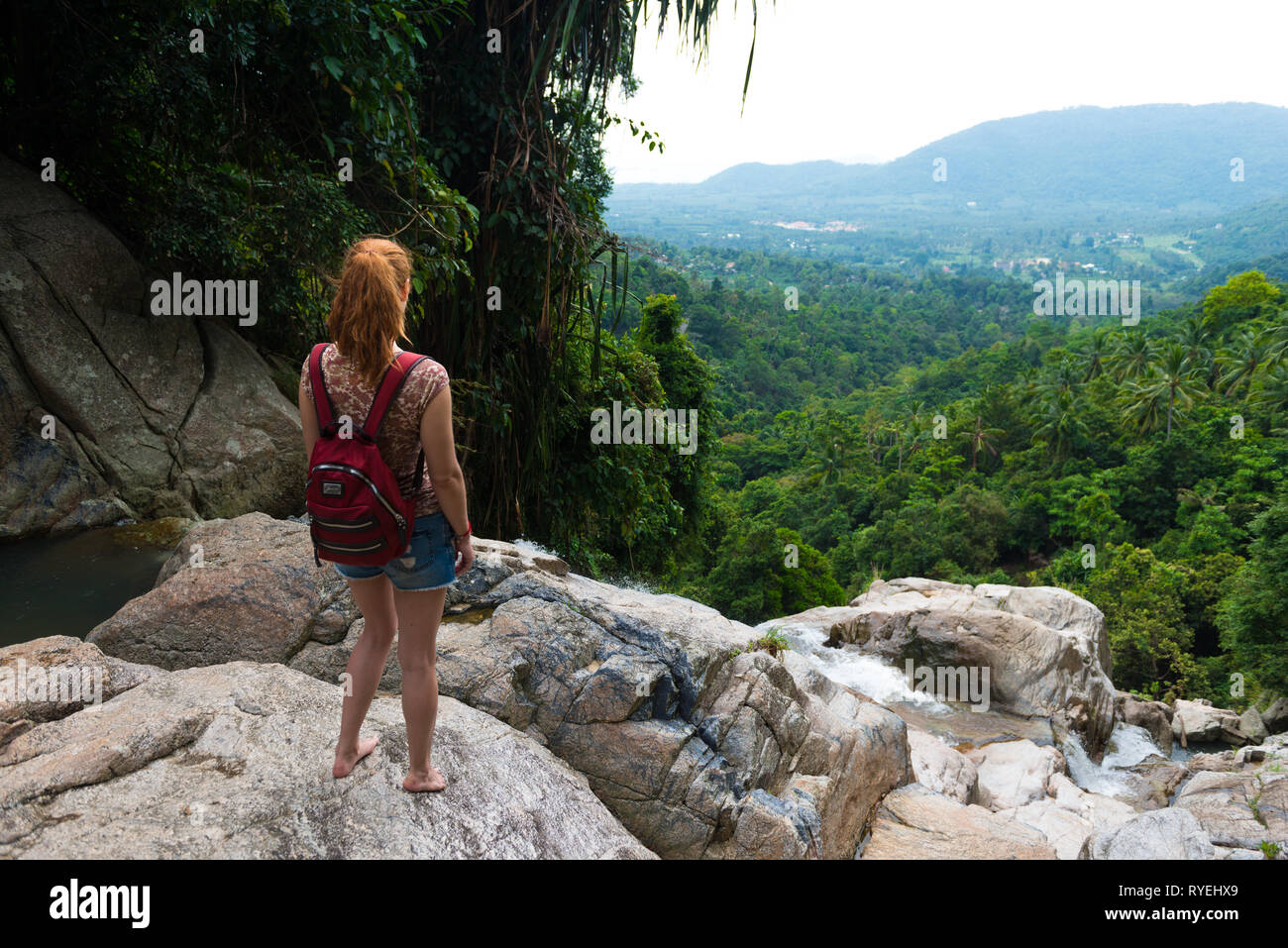 Girl standing on a cliff of Namuang waterfall, observing the nature of Samui island, Thailand Stock Photo