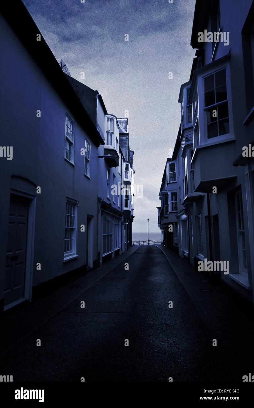 Dark and foreboding narrow coastal  back street with encroaching houses - Stock Image