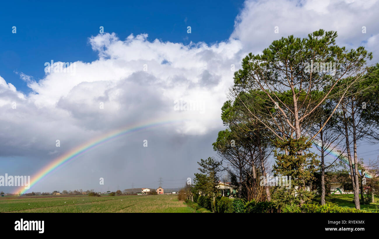 Beautiful complete rainbow over the countryside of the province of Pisa, Tuscany, Italy, Europe - Stock Image