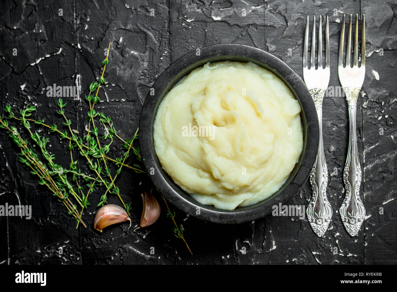 Mashed potatoes in a bowl with garlic and thyme. On black rustic background. - Stock Image
