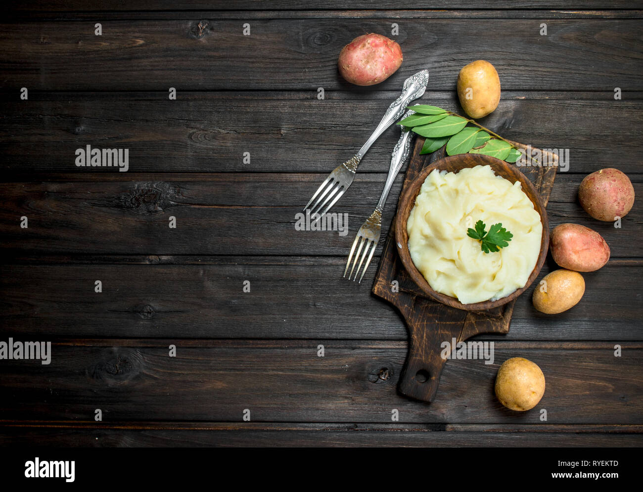 Mashed potatoes with a sprig of parsley . On a wooden background. - Stock Image
