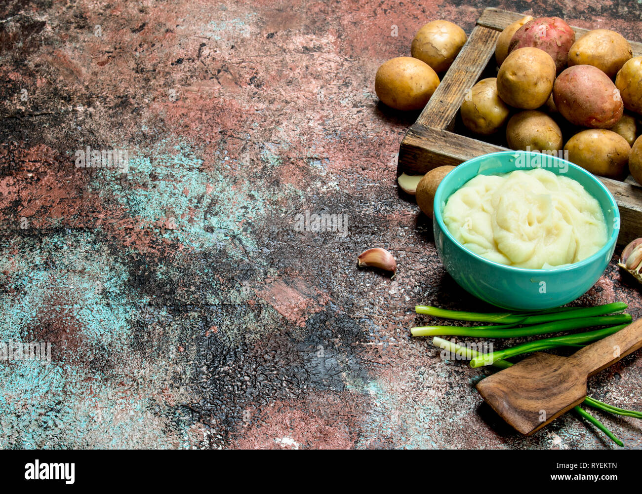 Mashed potatoes in a bowl with green onions . On a rustic background. - Stock Image