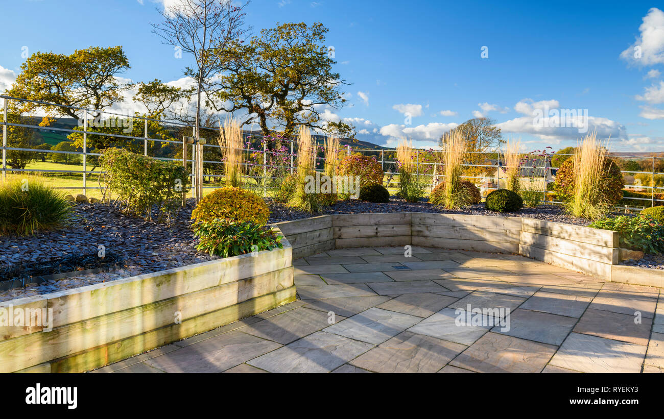 Autumn colours in beautiful, private garden, Yorkshire, England, UK - stylish, contemporary design, hard landscaping & planting in timber raised beds. - Stock Image