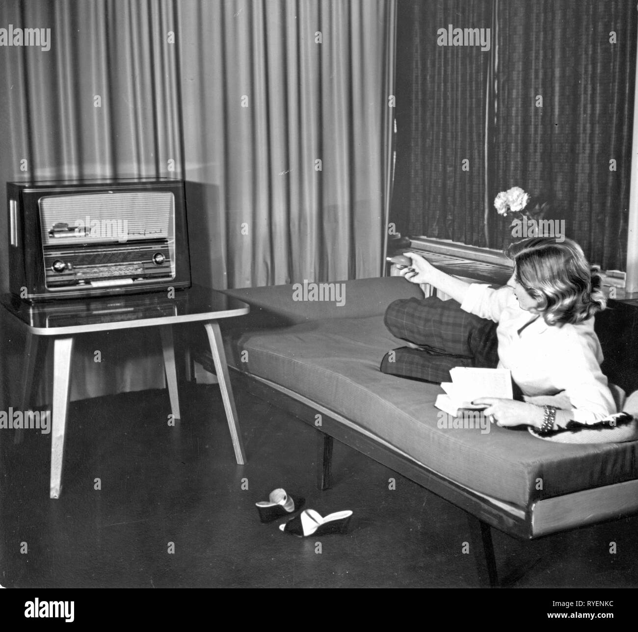 broadcast, radio, radio sets, Tonfunk Zauberperle W286F with 'magic switch', a young woman on a bed is operating the remote control, Germany, 1956, Additional-Rights-Clearance-Info-Not-Available - Stock Image