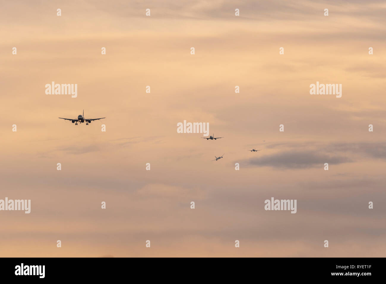 Queue of planes on final approach to land at London Heathrow Airport, London, UK at dawn. Landing airliners. Busy finals for landing at airport - Stock Image