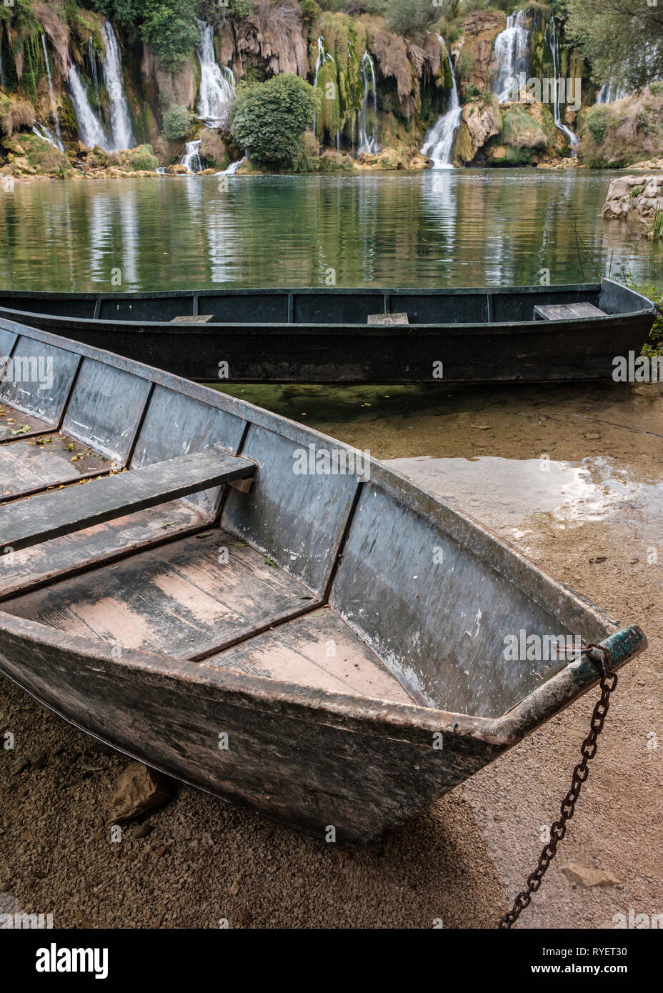 Two wooden boats moored on the shoreline of the Trebizat River with Kravice Falls in the background, Herzegovina, Bosnia and Herzegovina - Stock Image