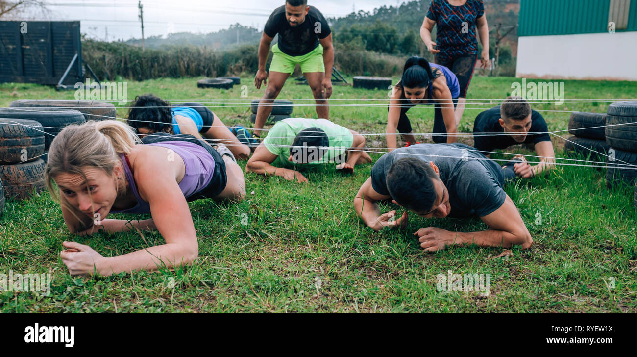Participants in an obstacle course crawling Stock Photo