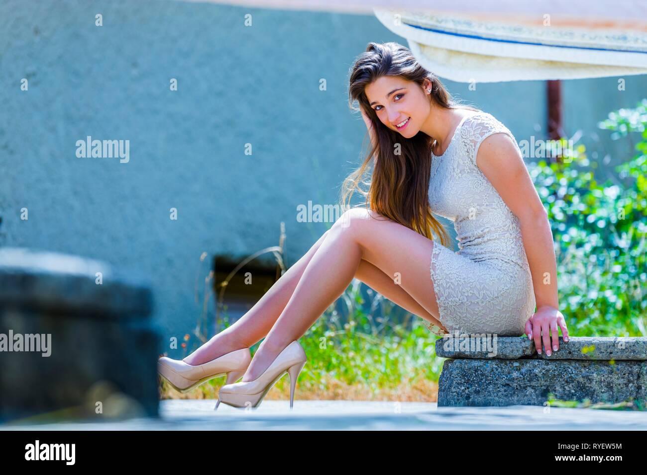 Pretty teen girl outside legs heels seated smiling brunette hair - Stock Image