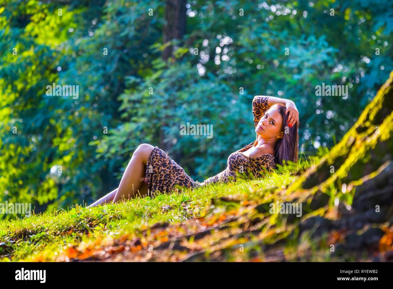 Pretty teen girl outside lying on back in nature wearing leopard-patterned dress - Stock Image
