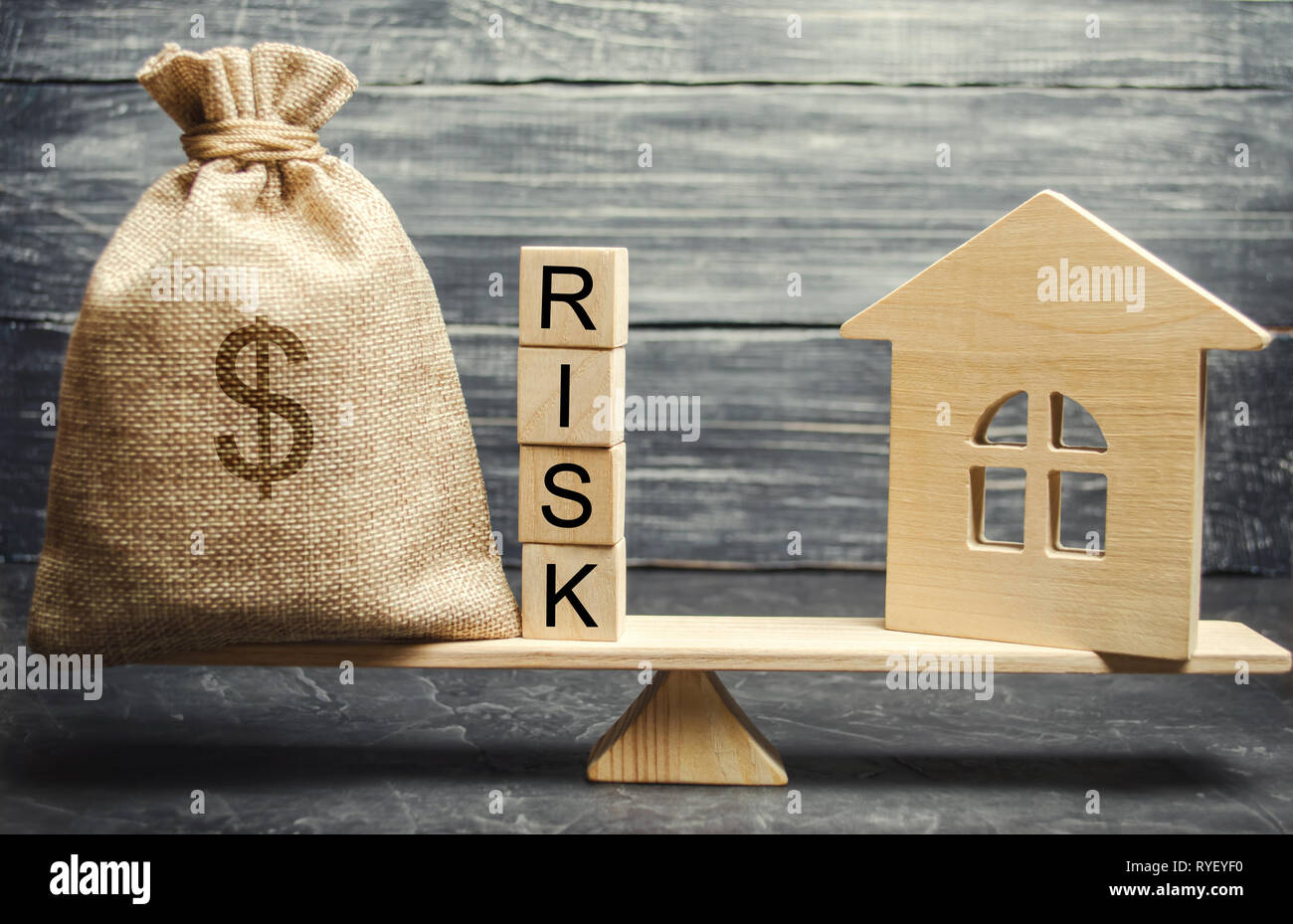 Money bag, blocks with the word Risk and a wooden house on the scales. The concept of losing money when investing in real estate. Risks of losing a ho Stock Photo
