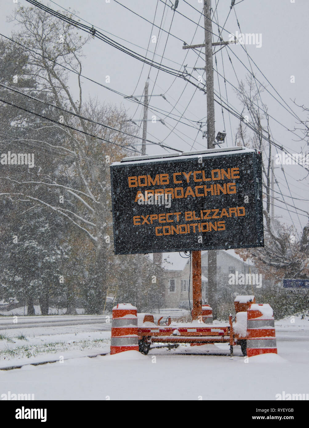 Electric road traffic mobile sign by the side of a snow covered road with snow falling warning of BOMB CYCLONE approaching, expect blizzard conditions - Stock Image