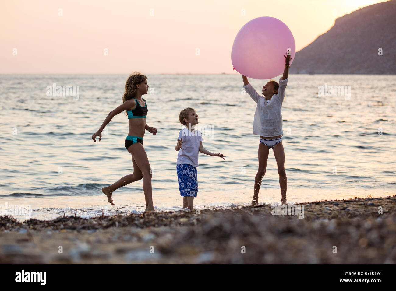 Three children playing with huge pink balloon on beach at sunset. Siblings on vacations at sea. Stock Photo