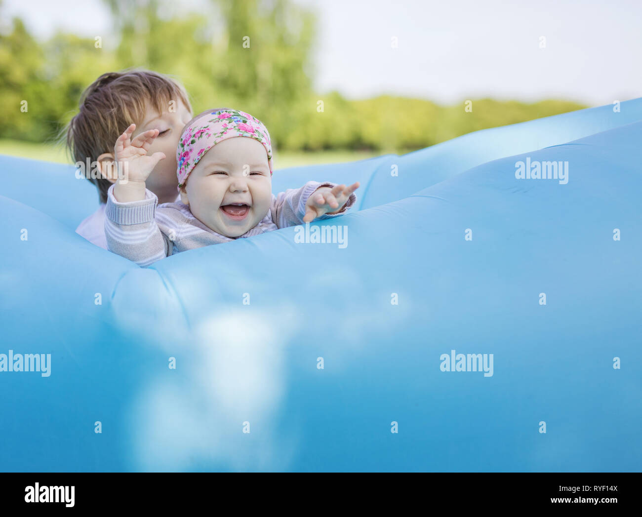Siblings playing on inflatable sofa outdoors. Baby girl and older brother having fun together in park. Stock Photo