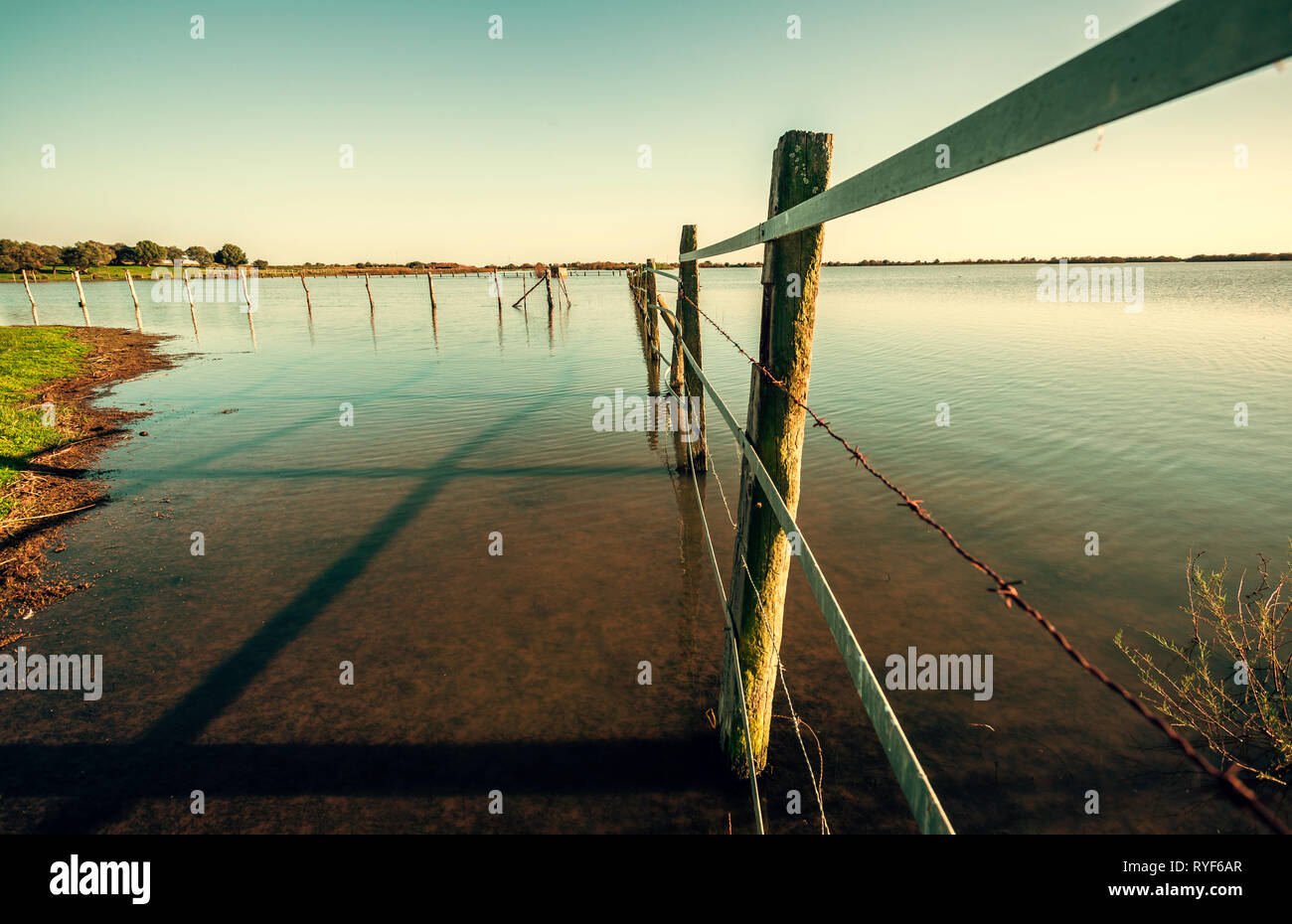 Old rusty barbed wire fence and wooden post against lake and sky - Stock Image