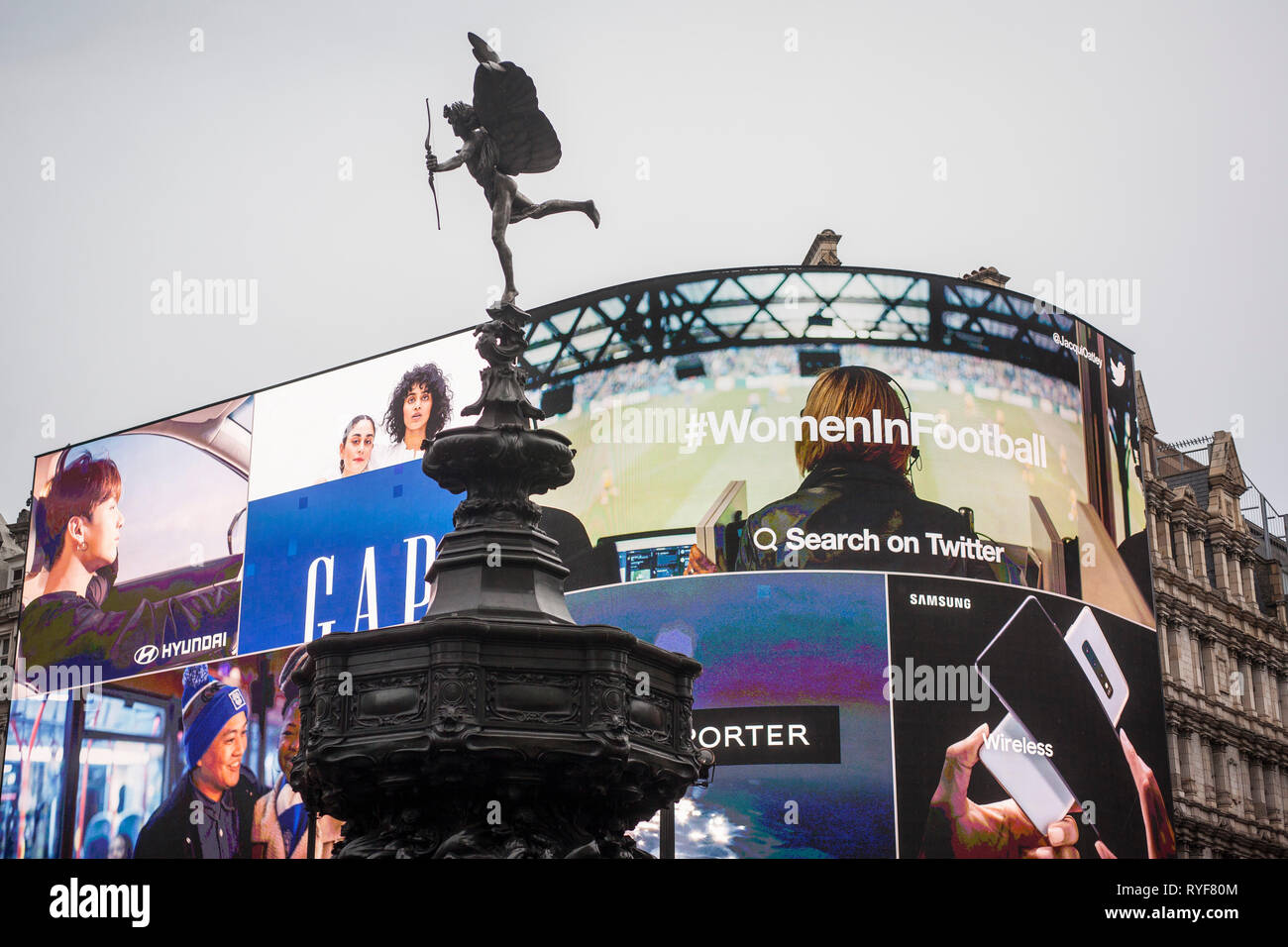 The Eros statue in Picadilly with the giant illuminated advertisng billboards behind. - Stock Image