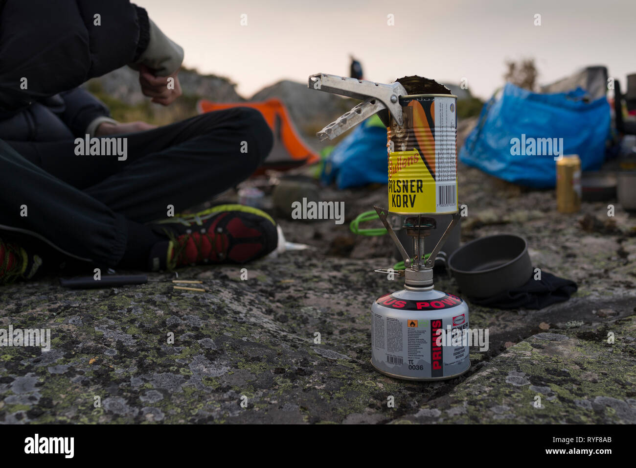 Cooking a can of sausage on a camping stove. Bullens pilsnerkorv - Stock Image