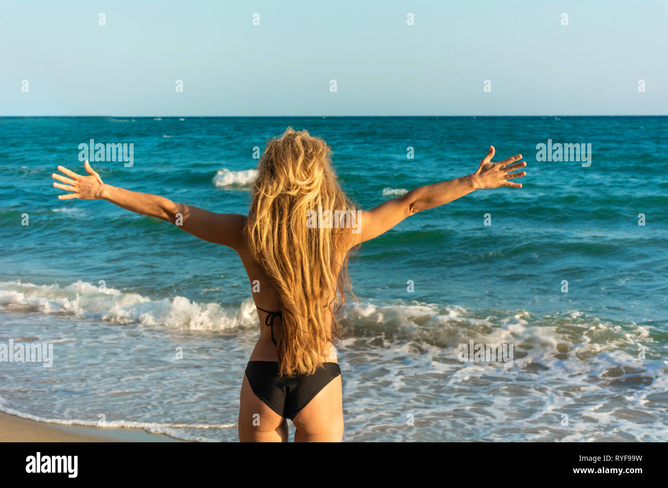 Concept of woman spreading hands embracing freedom new life happiness life goals success - Rear view of girl on beach wide open raised arms - Happy yo Stock Photo