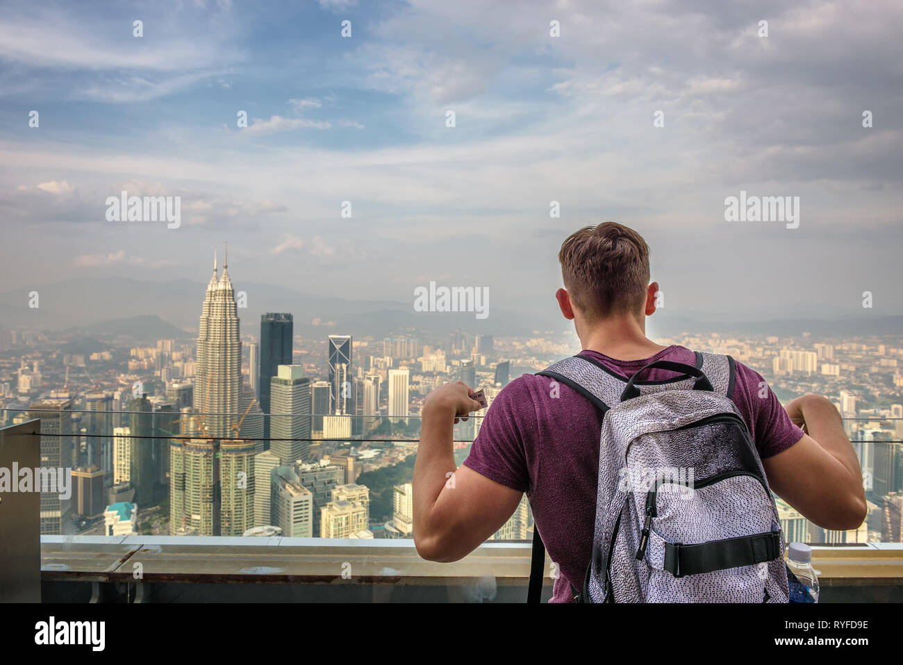 Tourist with a backpack enjoys the panoramic view of the Kuala Lumpur skyline - Stock Image