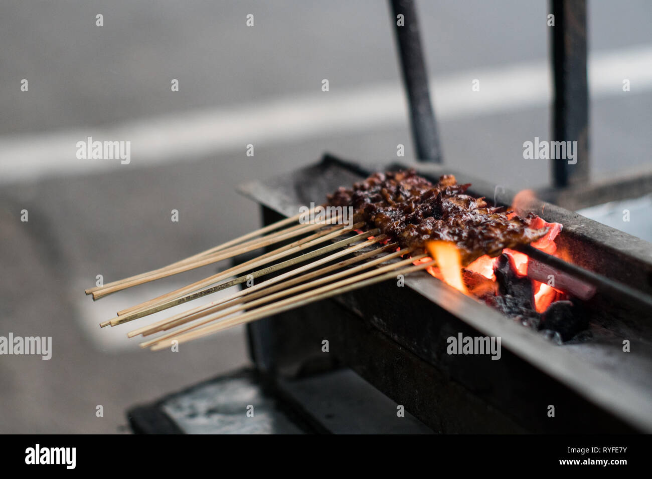 Chicken satay with rice cake (lontong), a street food that you can find everywhere in Indonesian street. Stock Photo