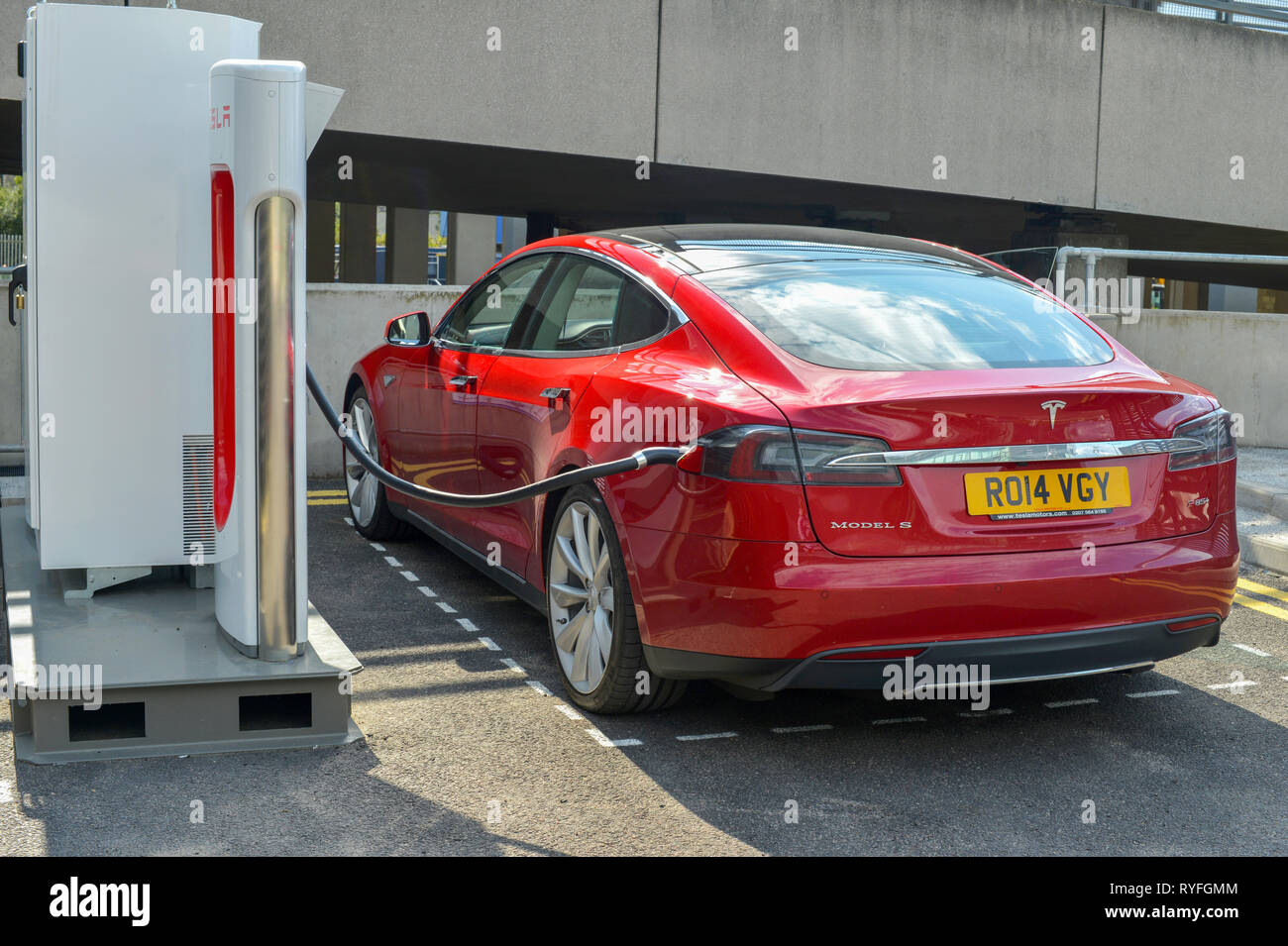Tesla Model S electric car charging at a Supercharger station - Stock Image