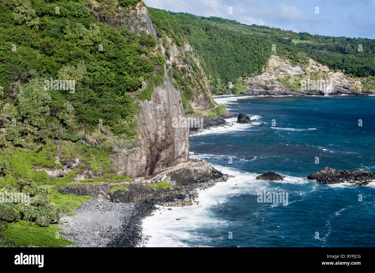Maui Cliff Road:  A narrow road curves around a cliff face as the Piiliani Highway skirts the coastline of eastern Maui. - Stock Image