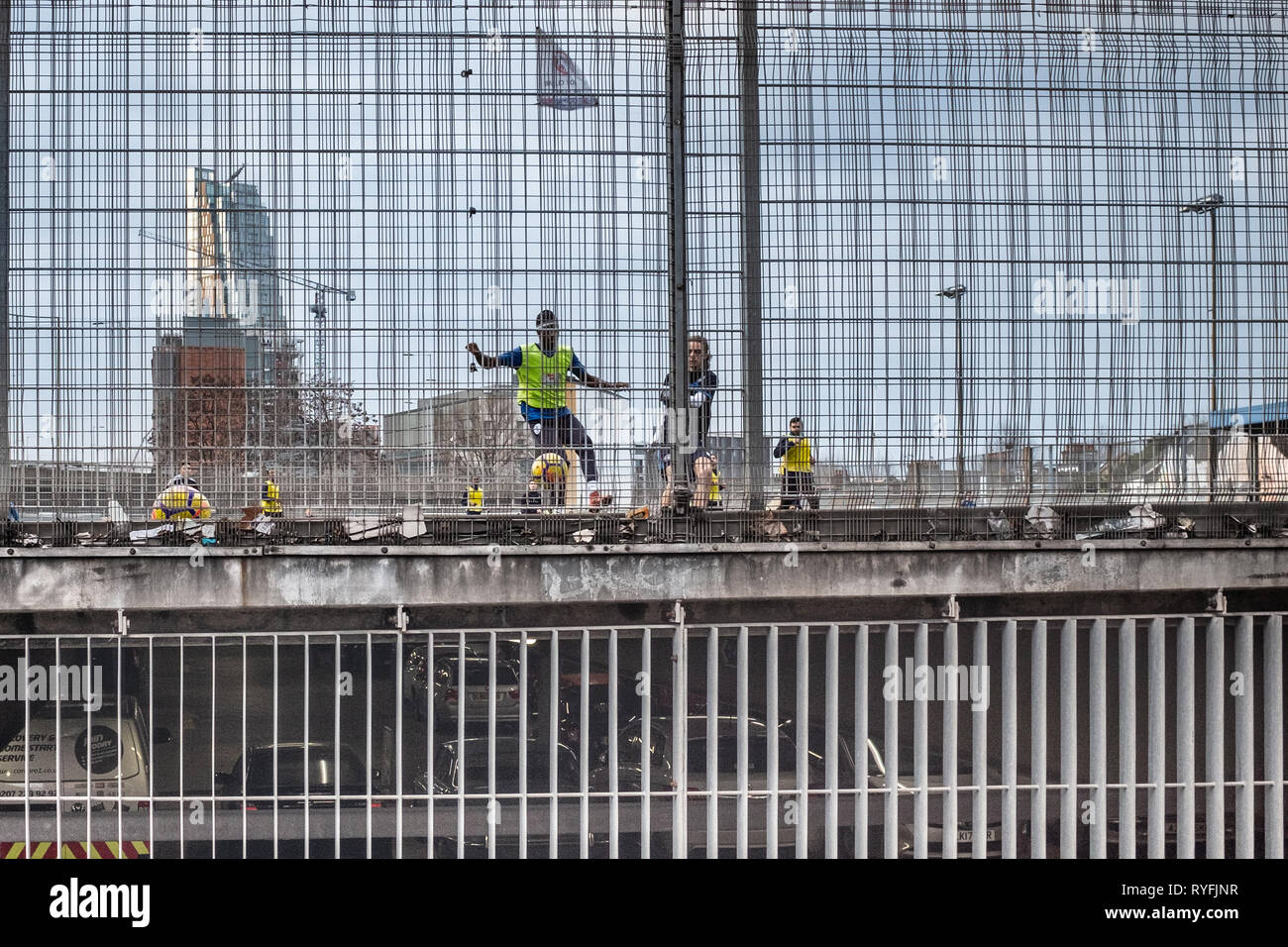 Football being played in inner city urban space above a car perk - Stock Image