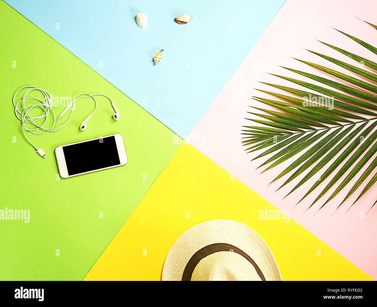 ee61ca6d Top view traveler accessories layout: tropical palm leaf, white straw hat,  mobile phone and headphones, seashells on colorful background.