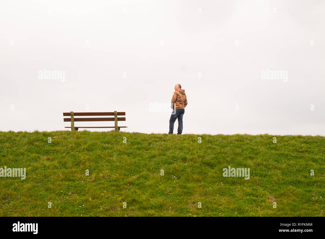 A single person standing next to a single empty wooden bench on the horizon - Stock Image