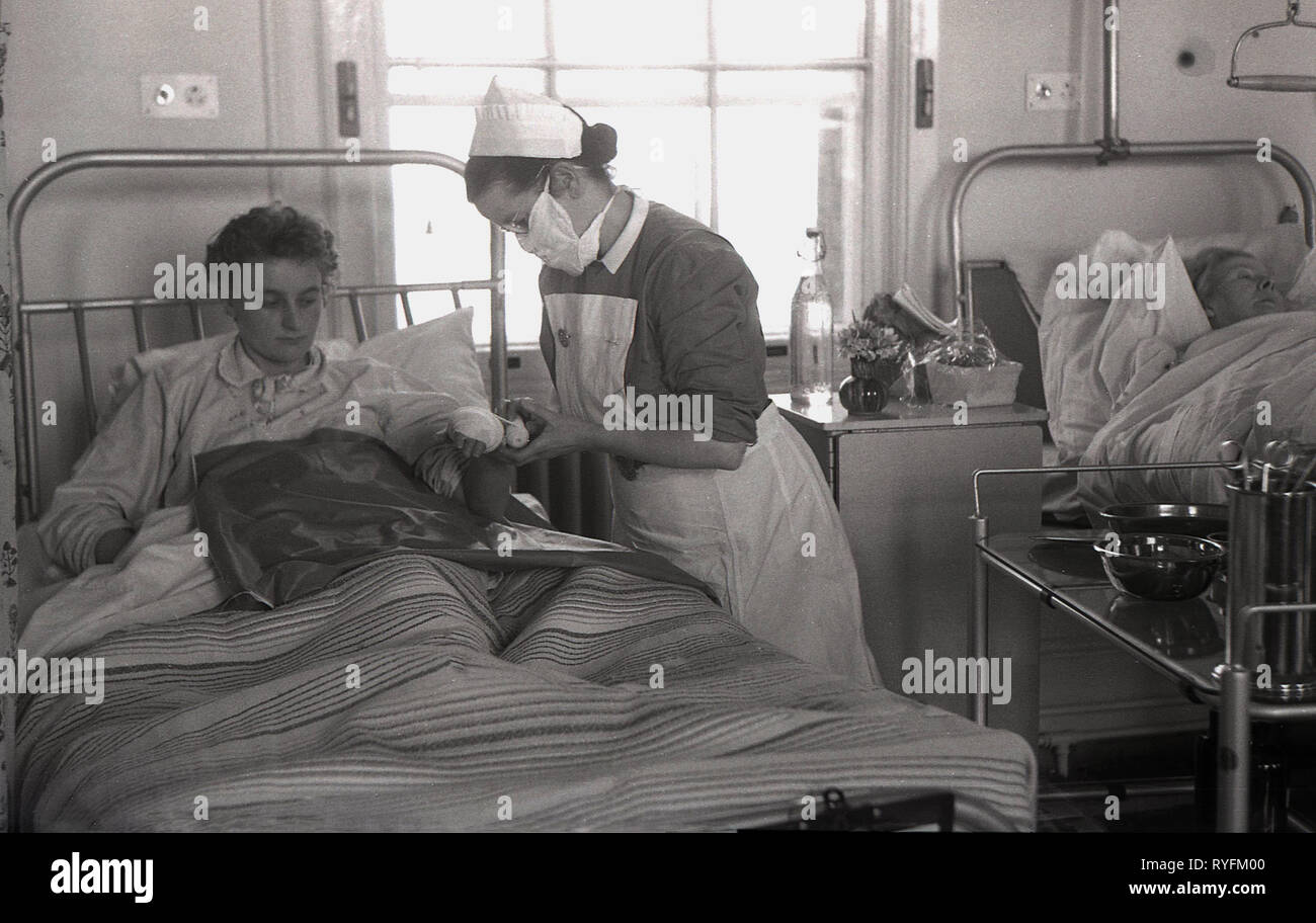 1940s, historical, on a hospital ward, a nurse treating the arm of a female patient lying in a metal hospital bed. - Stock Image