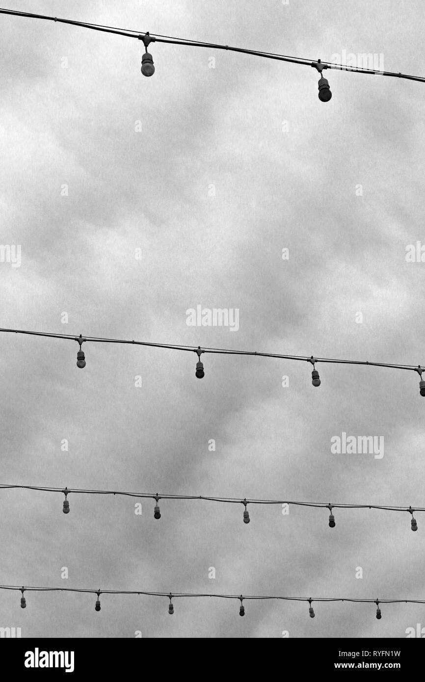 Unlit strings of lights strung across a street on a dreary day. - Stock Image