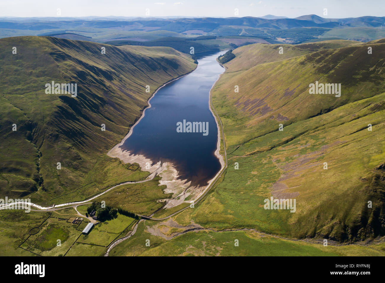 Aerial image of Talla Reservoir looking south towards distant Tinto Hill on a Summer afternoon. - Stock Image