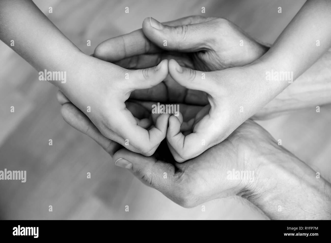 Children's hands form a heart in the hands of an adult. Black and white. - Stock Image