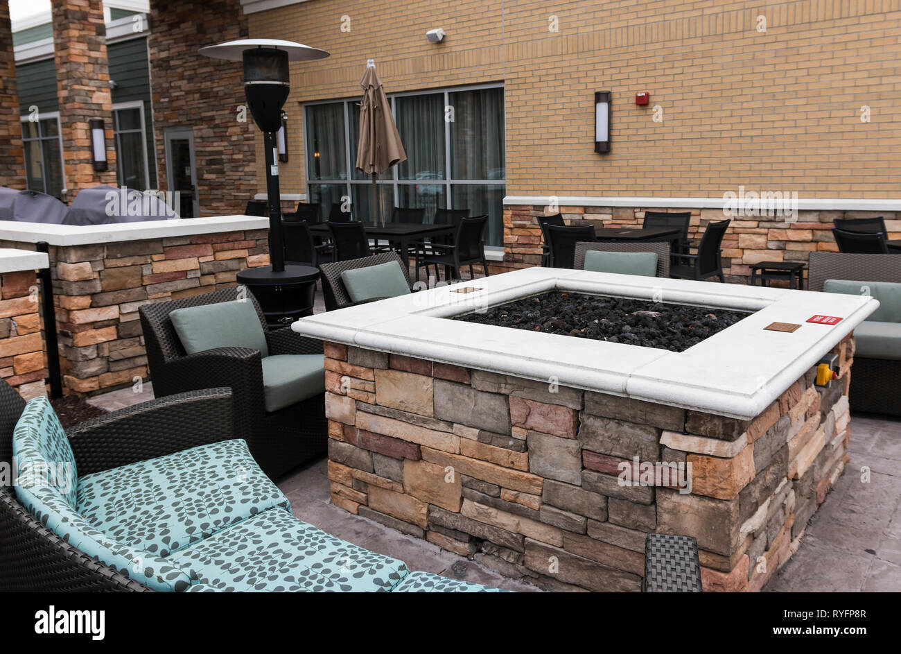 A relaxing area is set up outside of an upstate new york hotel that has a fire pit, couches, chairs and a heat lamp. - Stock Image