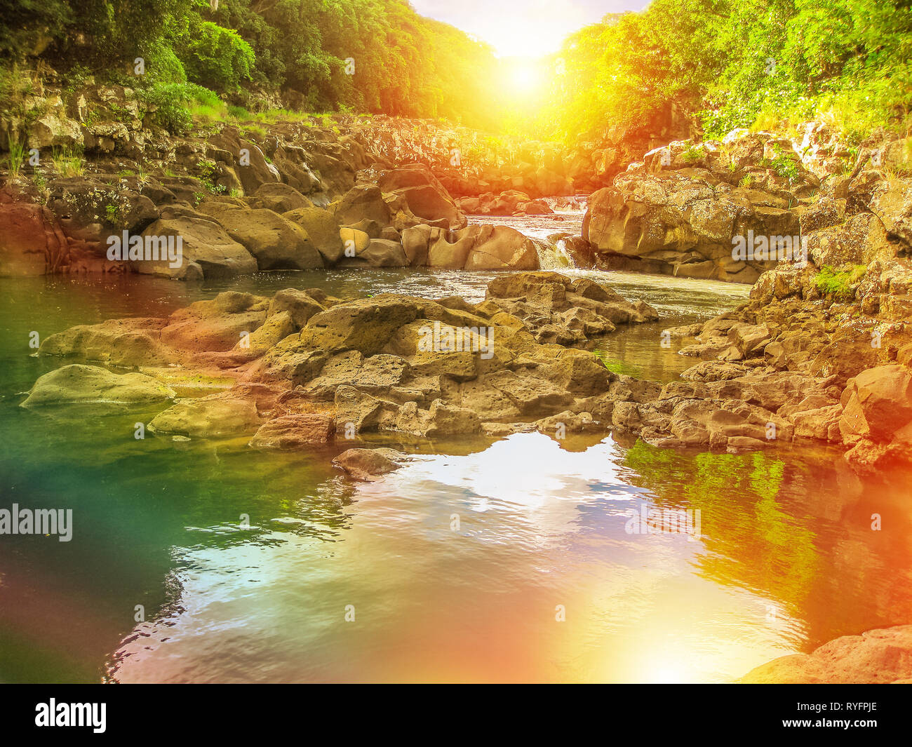Beautiful rainbow at Black River Gorges National Park, the largest protected forest of Mauritius, Indian Ocean, Africa. Scenic landscape reflected in - Stock Image