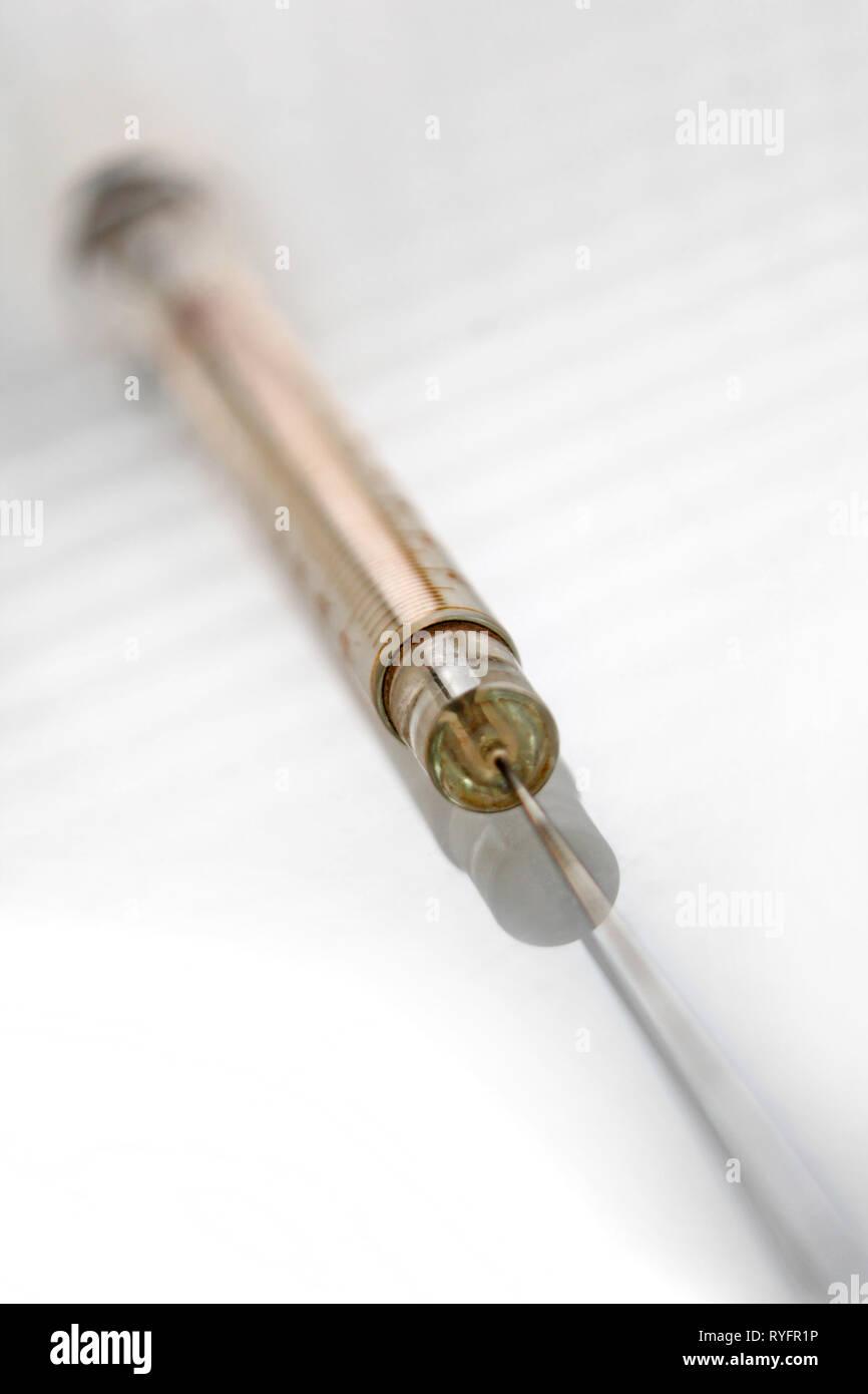 Vintage glass syringe, isolated on white background, close-up - Stock Image