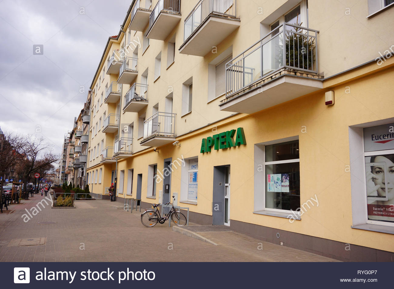 Poznan, Poland - March 8, 2019: Pharmacy store with parked bicycle in a apartment building by a sidewalk on the Slowackiego street. Stock Photo