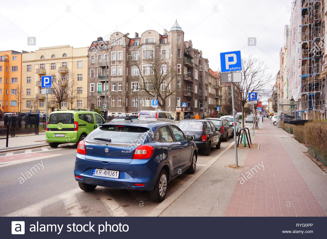 Poznan, Poland - March 8, 2019: Parked blue Suzuki Baleno car false parking by a sidewalk on the Slowackiego street in the city center. - Stock Image