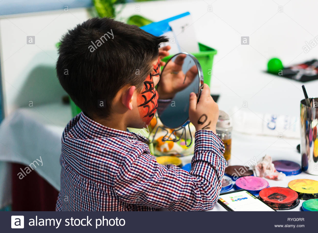 Poznan, Poland - March 2, 2019: Young boy watching his red painted face in a mirror during a birthday celebration party. Stock Photo