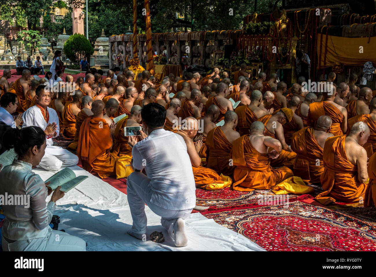 INDIA, BODH GAYA,Buddhist pilgrim taking a picture from his companion with a smart phone during prayer ceremony at the holy bodhi tree Stock Photo