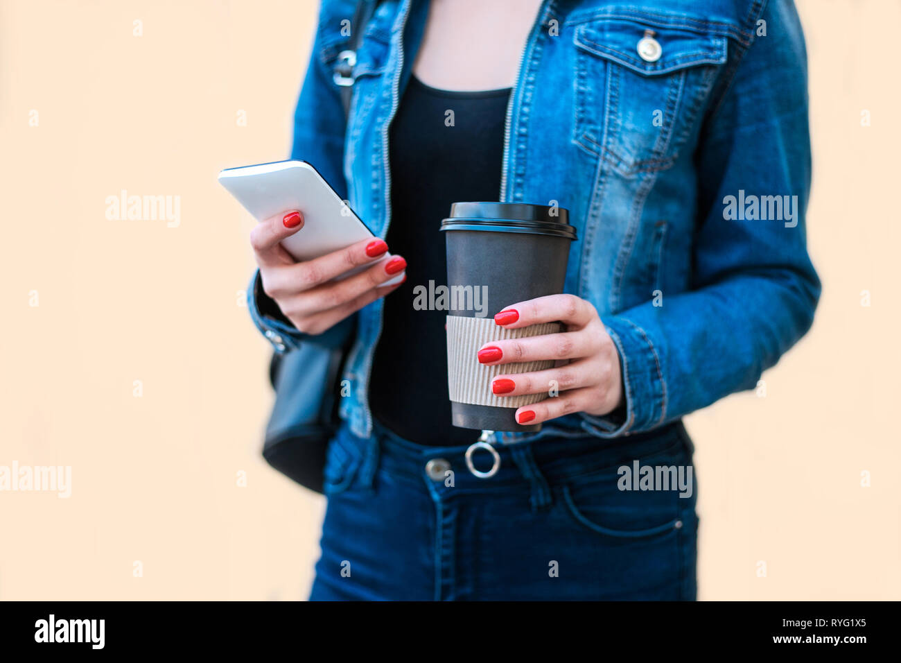 Woman hand holding coffee cup and smartphone. - Stock Image