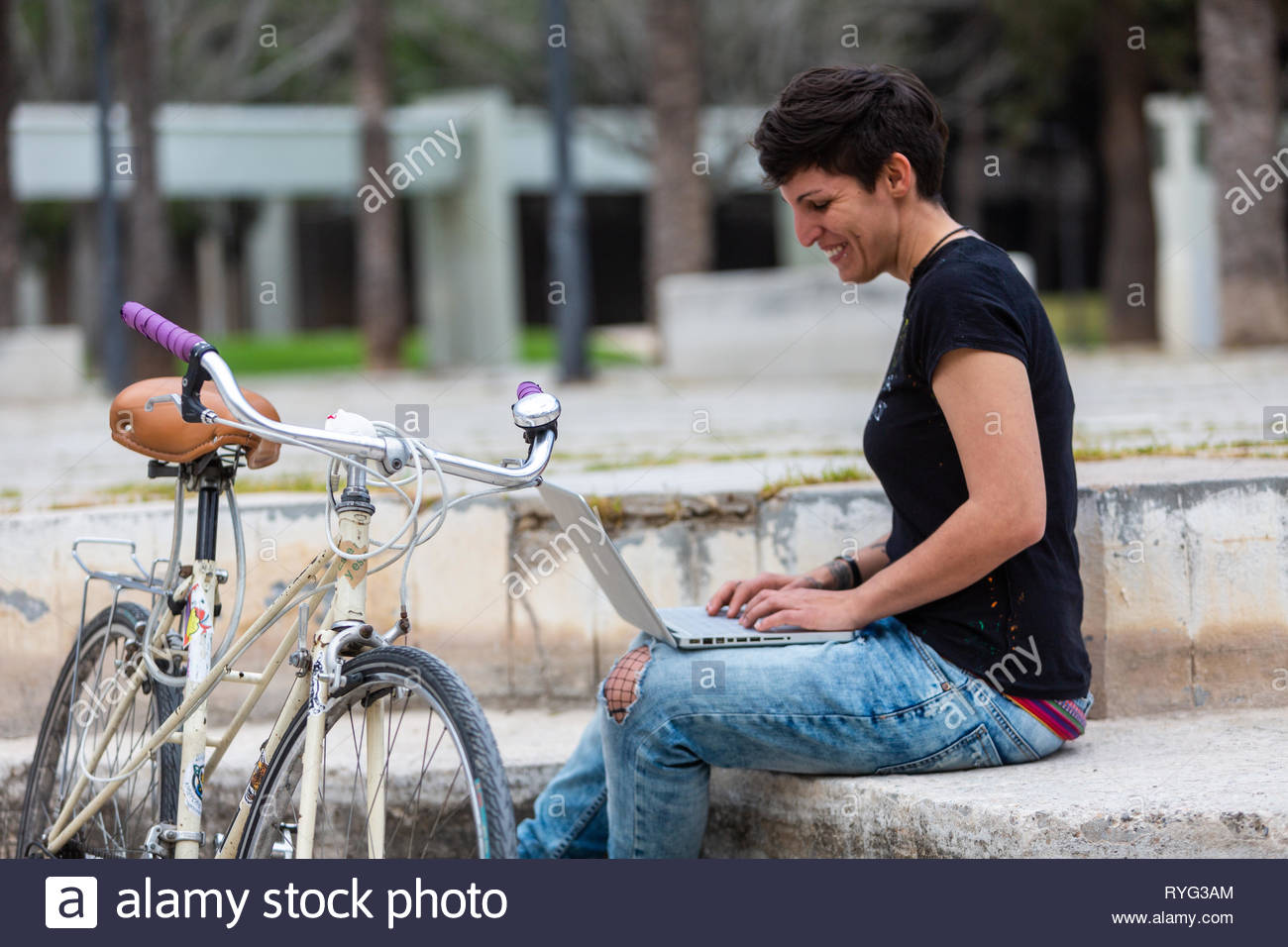 Woman with laptop and a bike outdoors - Stock Image