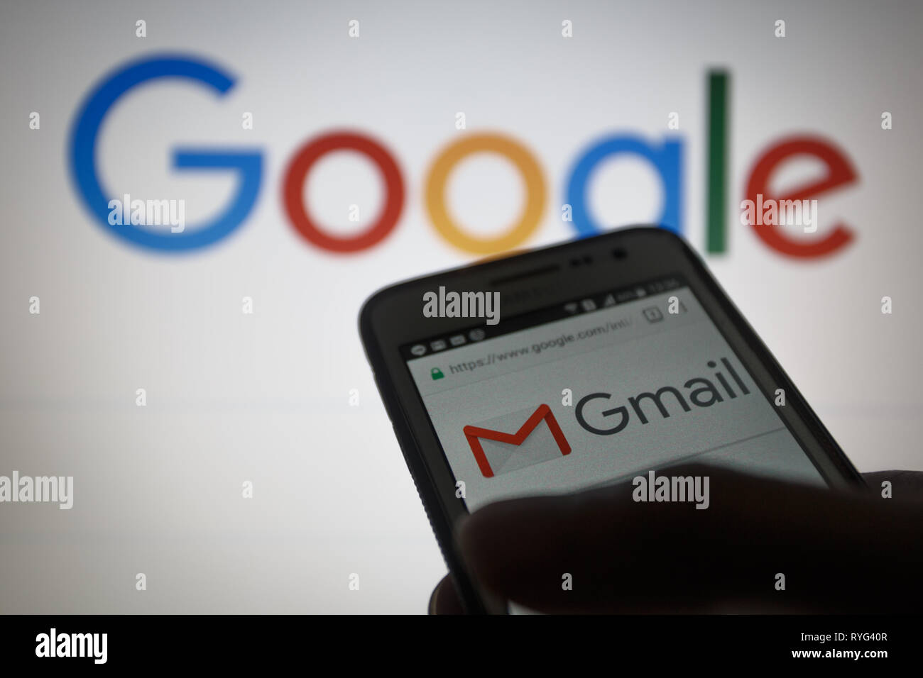 Gmail, free email service developed by Google. Logo on its website is seen on a smartphone display, Google logo unfocused on background - Stock Image