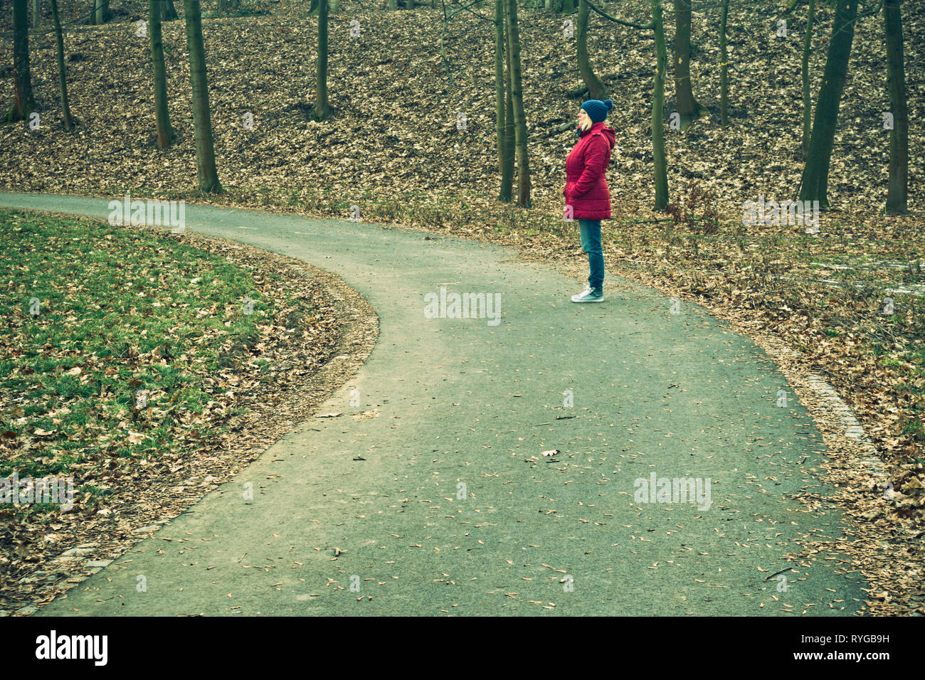 woman in red coat and blue knit hat standing on a road in nature, looking ahead, optimistic about the future - Stock Image